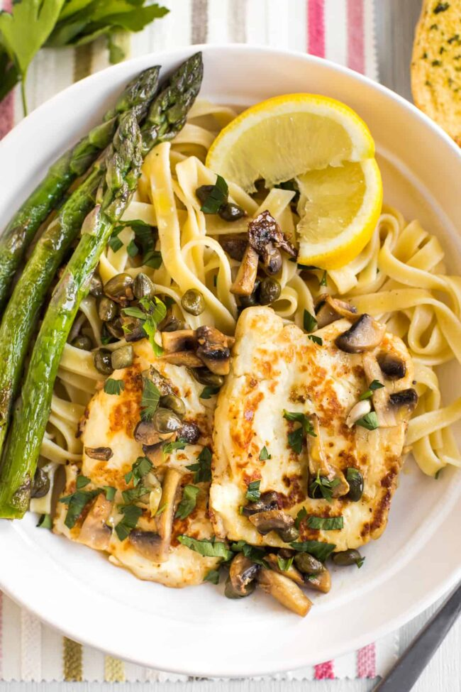 Portion of halloumi piccata served with tagliatelle and asparagus