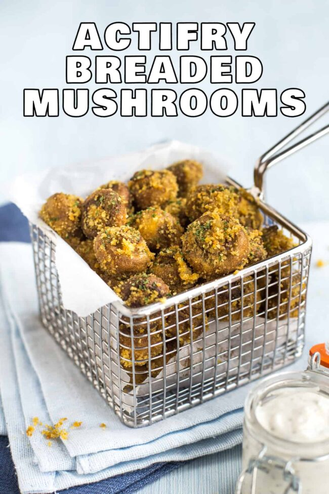 Portion of breaded mushrooms cooked in an Actifry air fryer and served in a fryer basket.