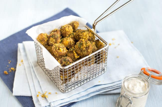 Portion of crispy breaded mushrooms served in a metal basket.