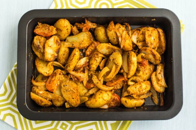Roasted Bombay potatoes with tomatoes and onions on a baking tray.