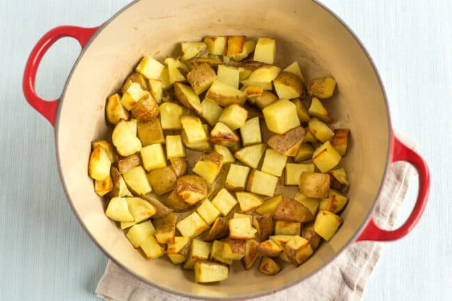 Potatoes roasting in a large casserole dish.