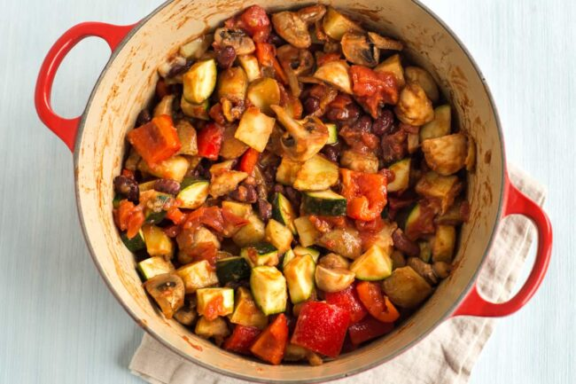Potatoes and vegetables in tomato sauce in a large casserole dish.
