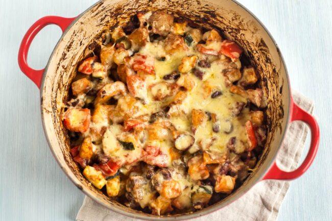 Cheesy bean and potato bake in a large casserole dish.