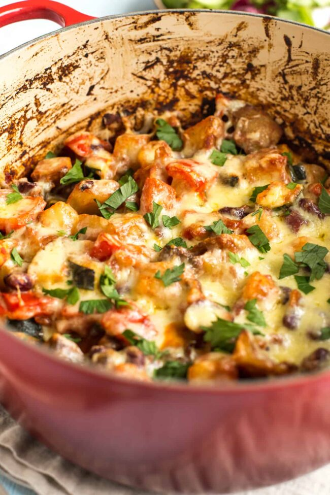 Cheesy Mexican bean and potato bake in a large casserole dish topped with cilantro.