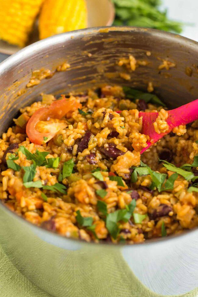 Vegan jambalaya in a saucepan topped with fresh parsley