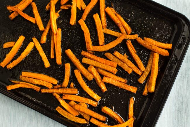 Roasted carrot sticks on a baking tray.