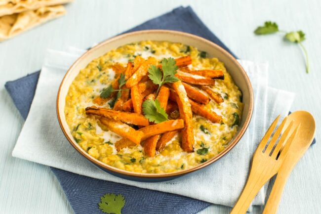Portion of creamy dal in a bowl topped with roasted carrots and cilantro.