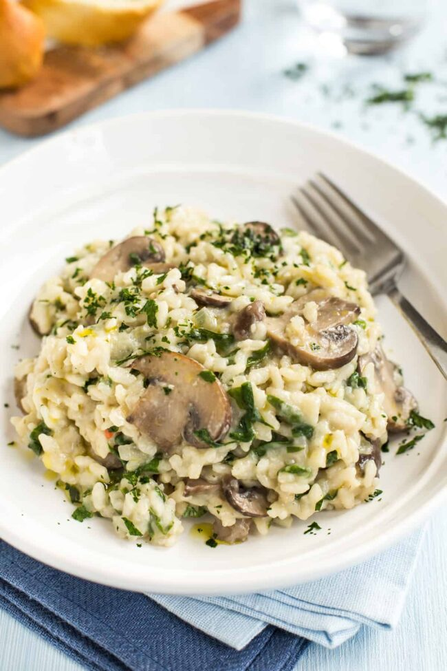 Portion of mushroom and spinach risotto in a bowl with a fork.