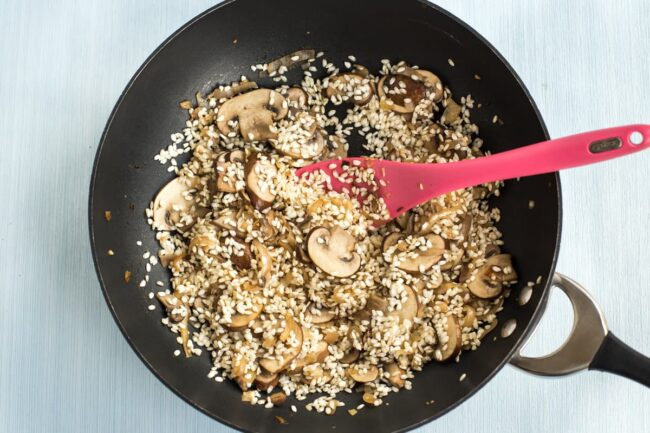 Risotto rice dry frying in a wok with mushrooms.