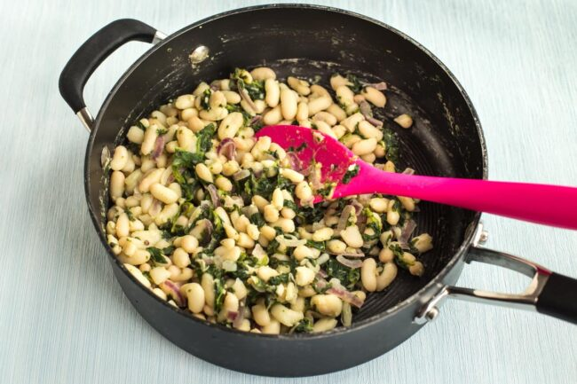 White beans cooking in a pan with spinach.