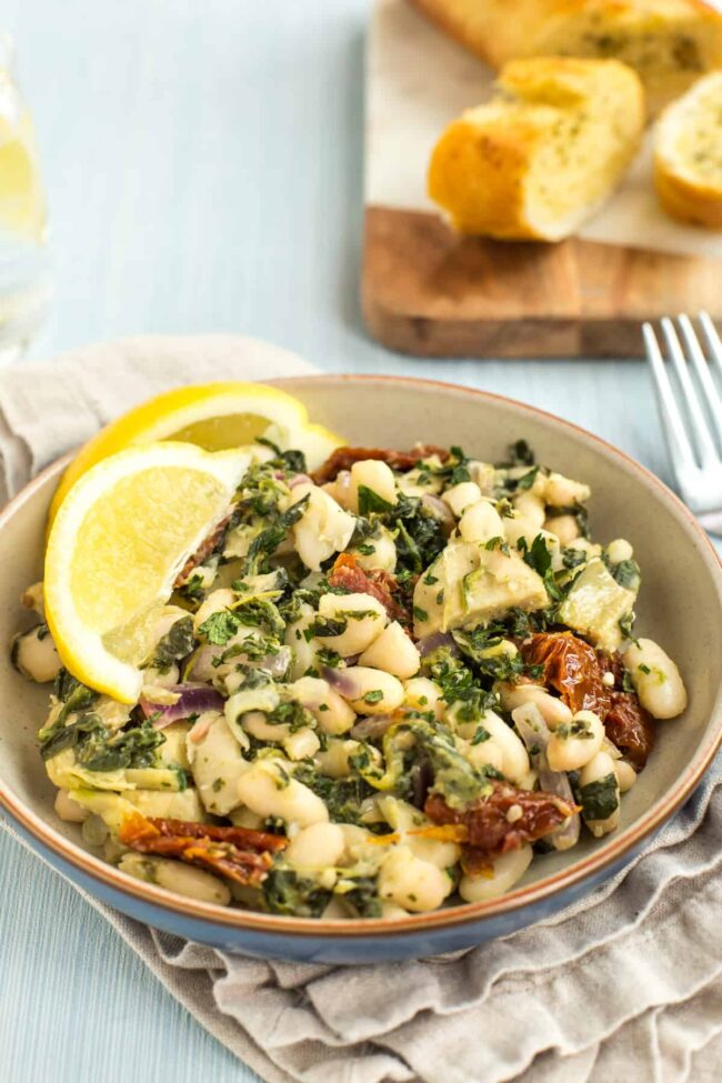 Portion of Tuscan beans with spinach and sun-dried tomatoes.