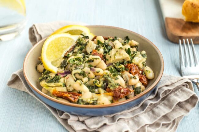 Portion of Tuscan beans in a blue bowl with spinach and sun-dried tomatoes.