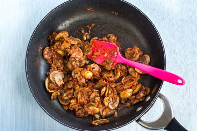 Rich tomatoey mushrooms cooking in a frying pan.