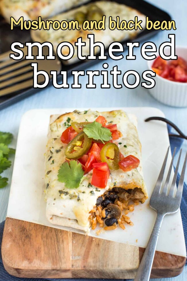 A vegetarian smothered burrito topped with tomatoes and jalapenos, with a scoop removed.