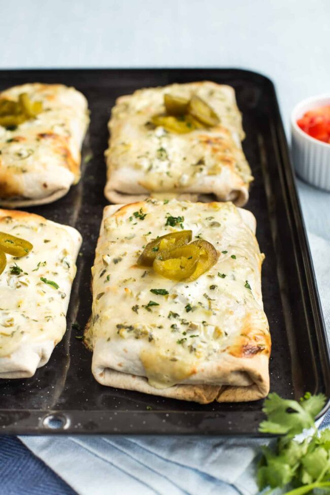 Vegetarian smothered burritos topped with jalapenos on a baking tray.
