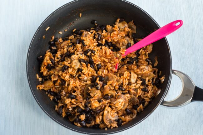 A mushroom, rice and black bean burrito filling cooking in a pan.