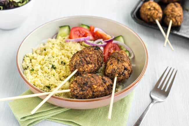 Vegetarian koftas on sticks, served in a bowl with couscous and tomato salad.