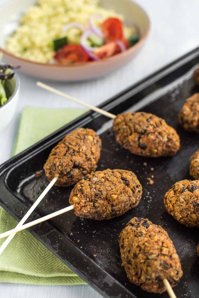 Vegan lentil koftas on a baking tray with skewers.