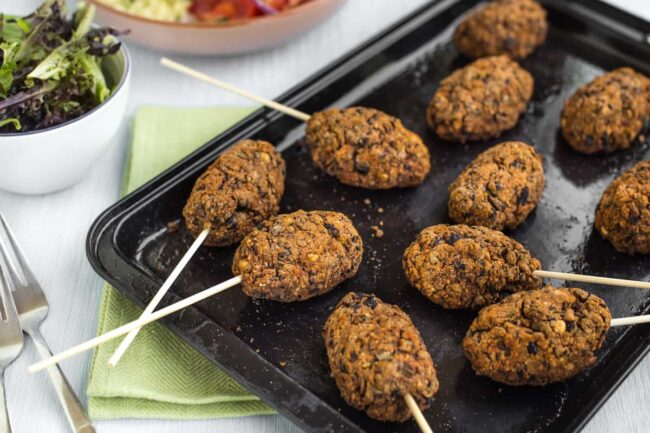 Vegan koftas on skewers on a baking tray.