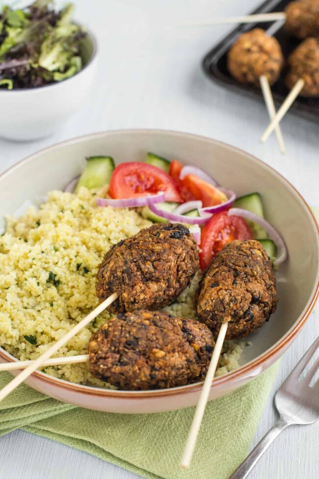 Vegetarian koftas on skewers, served in a bowl with couscous and tomato salad.