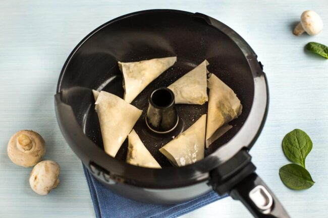 Uncooked homemade samosas in a Tefal Actifry pan.