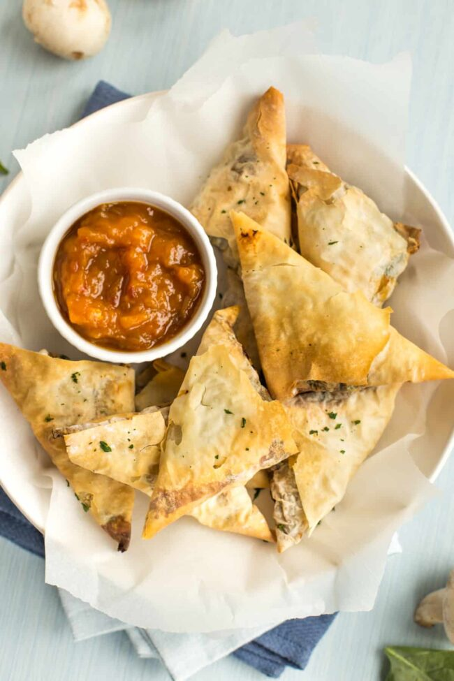 Tofu and spinach samosas with chutney, shot from above.