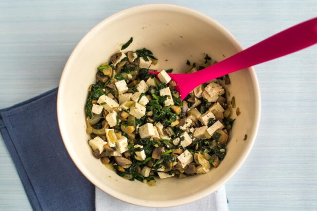 Vegetarian samosa filling in a bowl, with tofu, spinach and mushrooms.