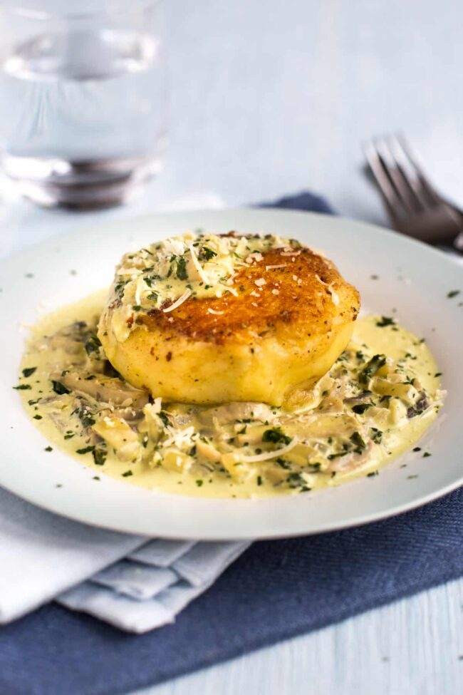 A crispy potato cake on a plate with a garlic cream sauce.