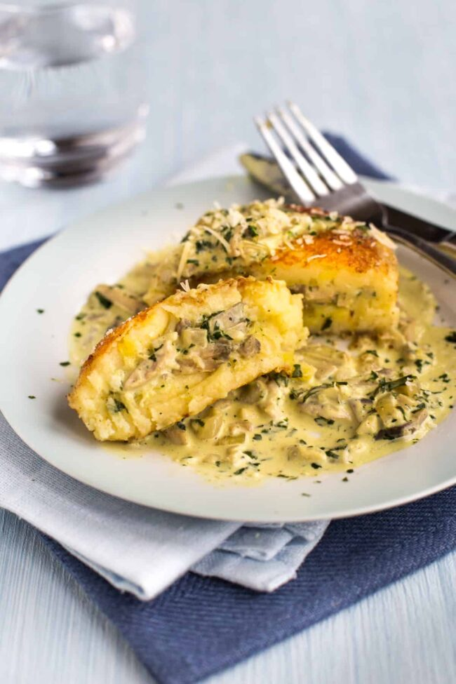 A cheesy mashed potato cake on a plate, cut in half to reveal a creamy mushroom filling.