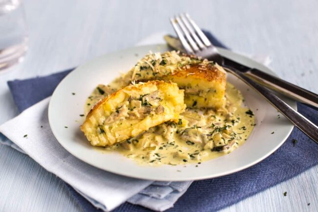 A cheesy mashed potato cake, stuffed with creamy mushrooms and served with a garlic cream sauce.