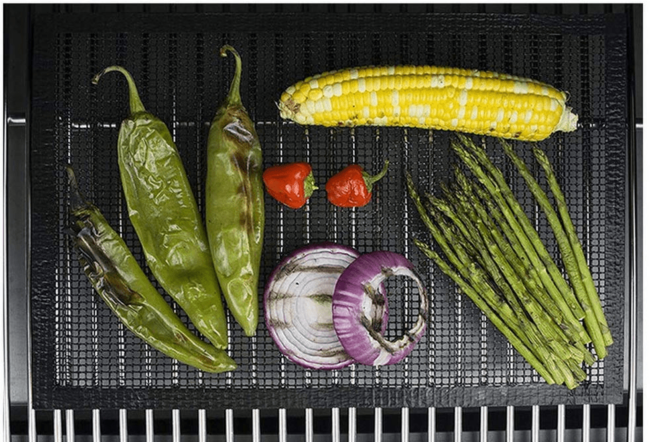A mesh BBQ grill mat being used to cook various vegetables.