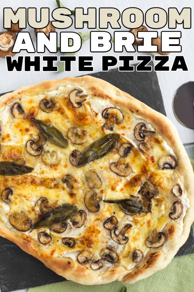 A white pizza topped with mushrooms and whole sage leaves.