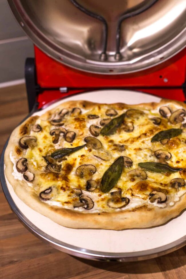 A cooked mushroom pizza inside a countertop pizza oven.