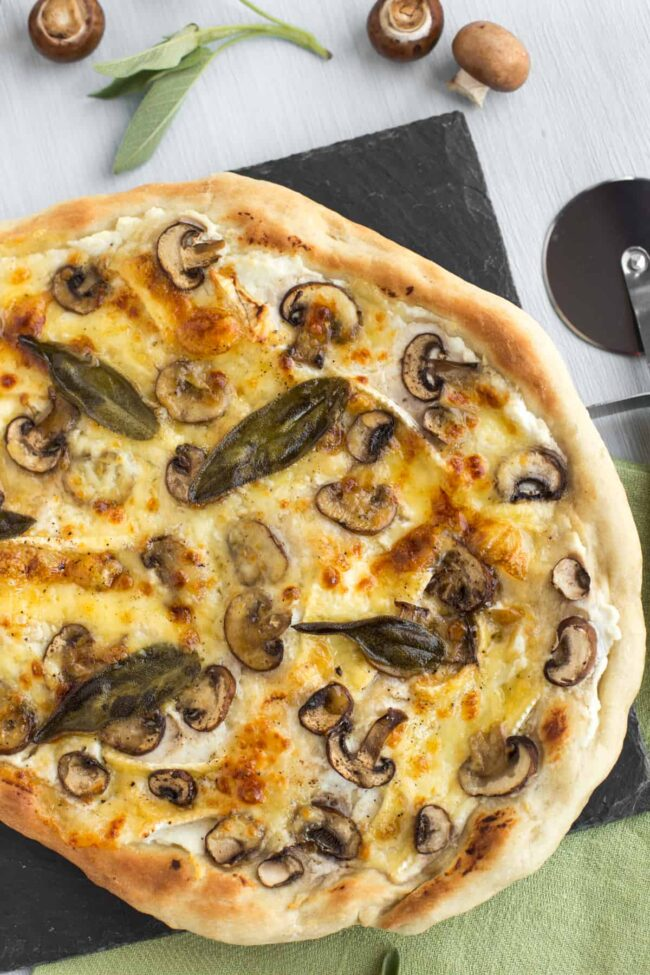 A crispy white pizza topped with mushrooms and sage.