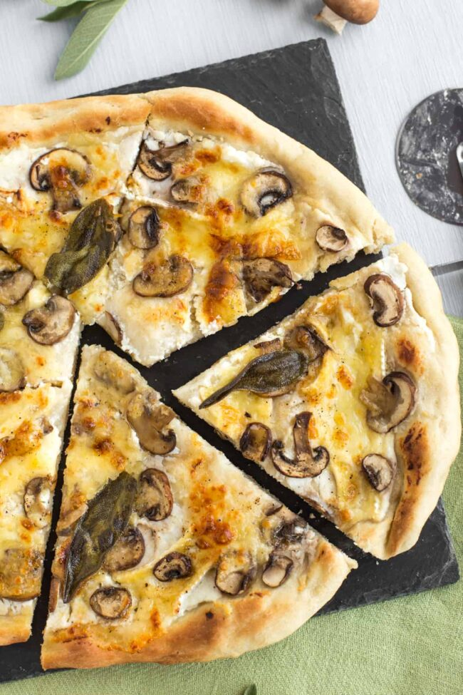 A white pizza topped with mushroom and sage, cut into wonky slices.