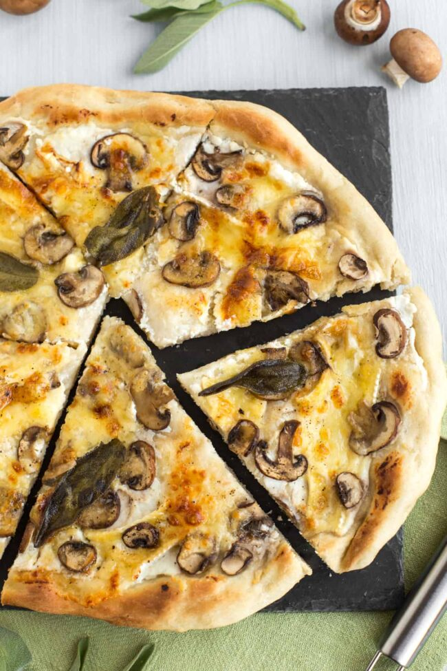 A vegetarian white pizza topped with mushrooms and sage leaves, cut into uneven slices.