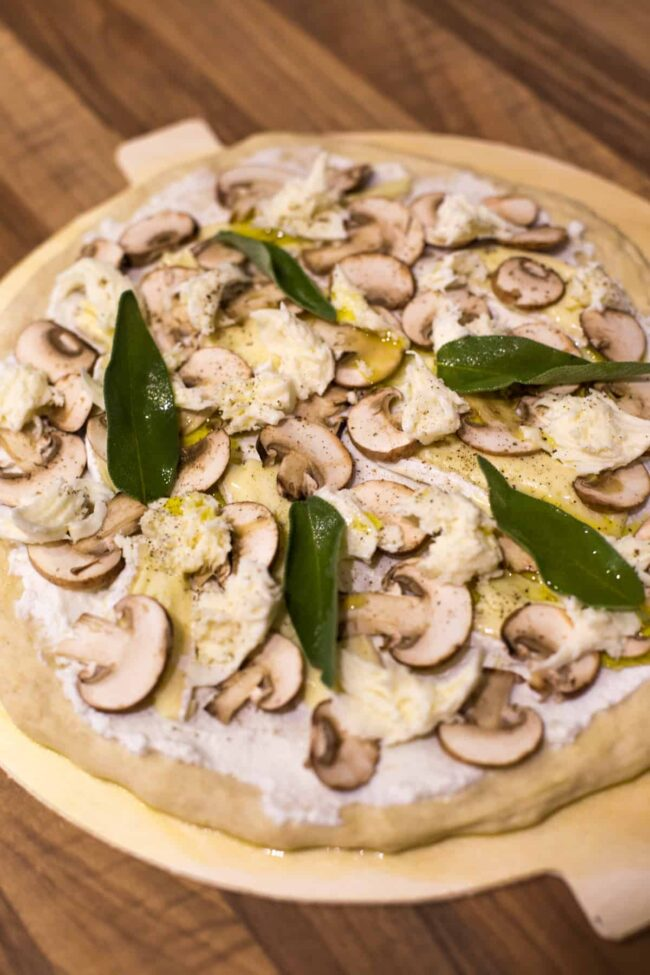 Close up photo of an uncooked white pizza topped with mushrooms and sage.