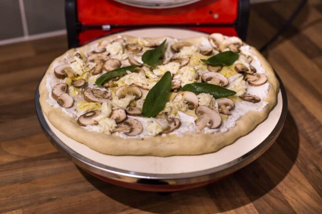 An uncooked mushroom pizza inside the Optima Pizza Express Napoli countertop pizza oven.