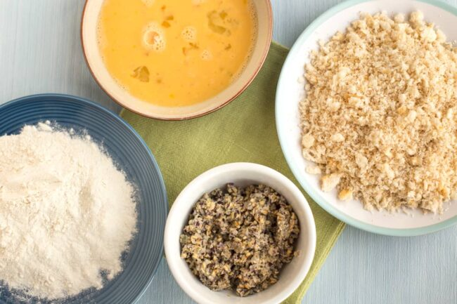 Ingredients for breading - flour, eggs, and breadcrumbs in small dishes.