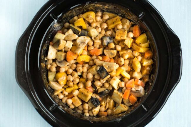Uncooked vegetables and chickpeas in a slow cooker pot.