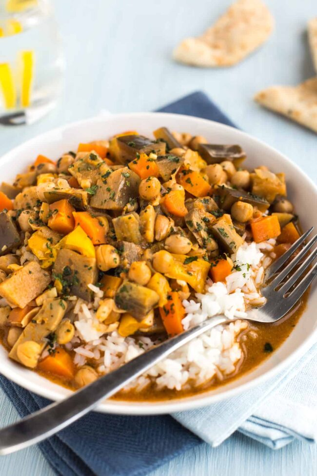 Bowlful of chickpea curry with vegetables and rice.