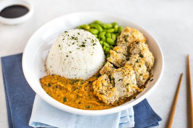 Vegan katsu curry on a plate with white rice and boiled edamame.