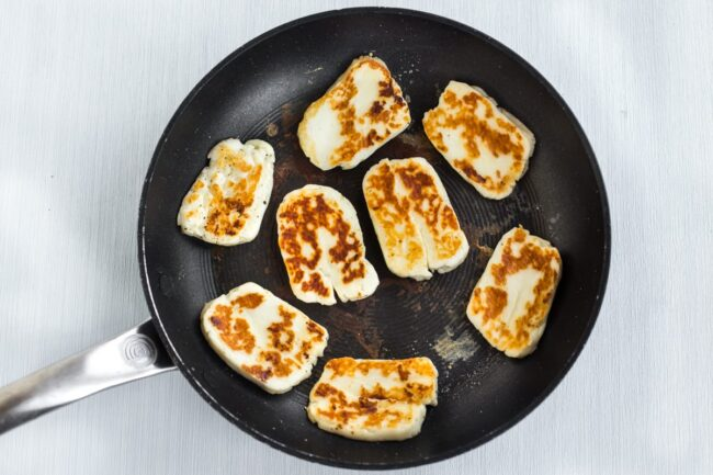 Grilled halloumi in a frying pan.