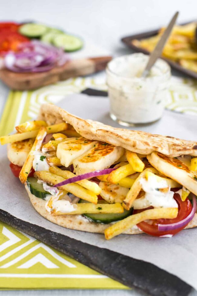 Grilled halloumi, French fries and salad inside a flatbread.