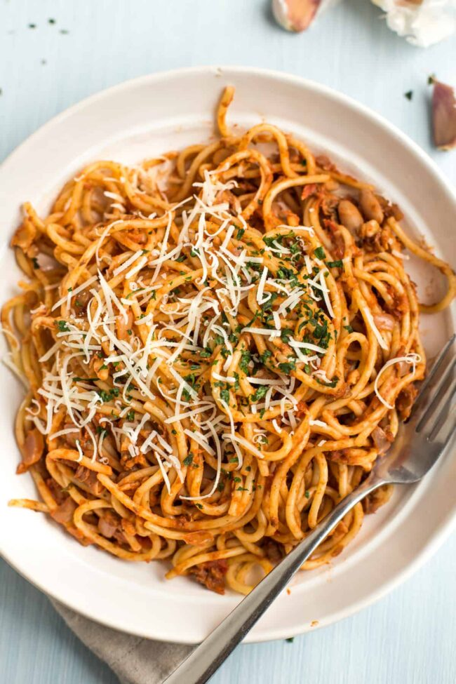 Portion of vegan spaghetti bolognese mixed together in a bowl topped with cheese and parsley.