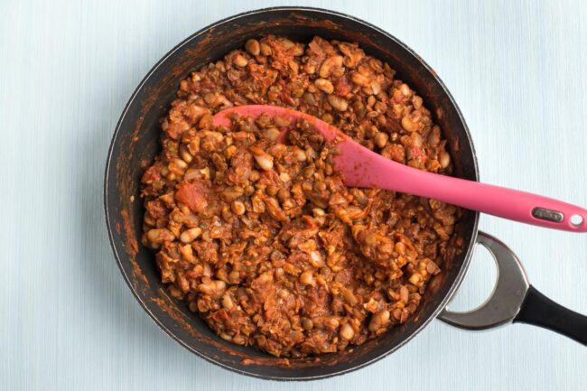 Rich tomato sauce in a frying pan with lentils and beans.