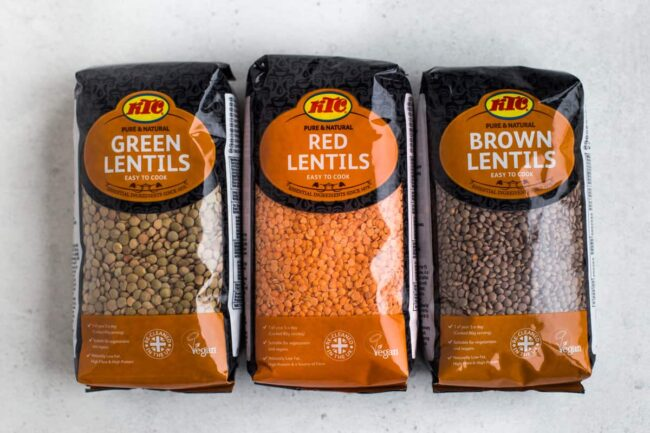 Packets of green, red and brown lentils next to each other.