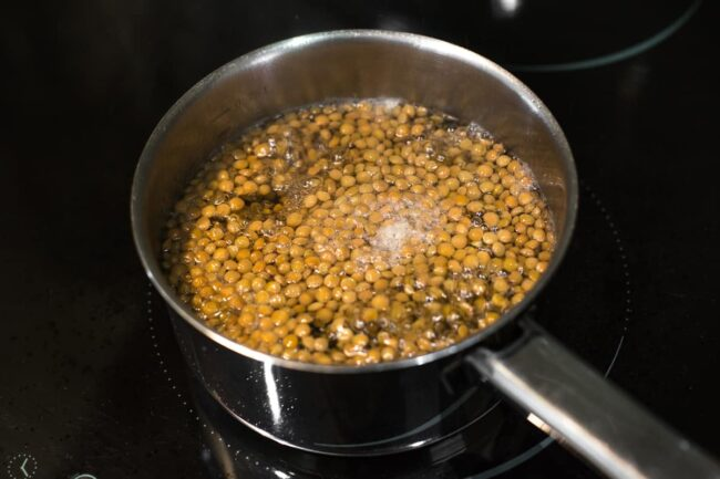 Brown lentils boiling in a saucepan in plenty of water.