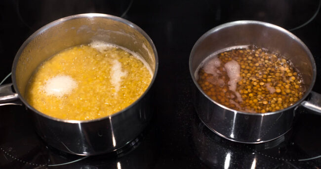 Red lentils and brown lentils cooking next to each other in two saucepans.