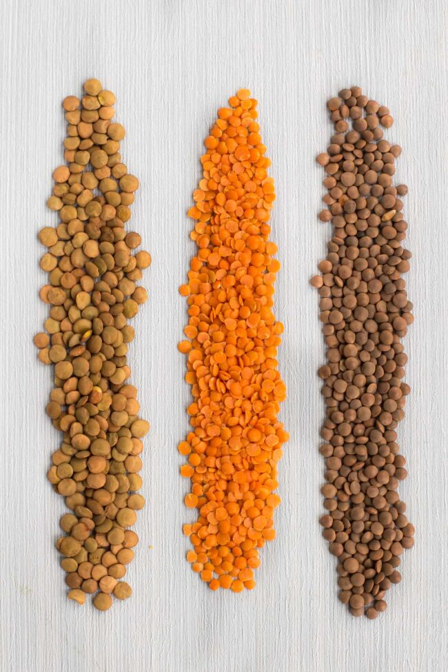 A comparison of green, red and brown lentils poured out onto a table.